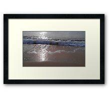 A gentle wave rolls onto a beach Framed Print