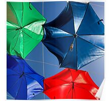 Colourful umbrellas strung up together on a blue sky background  Poster