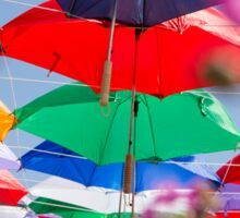 Colourful umbrellas strung up together on a blue sky background  Sticker