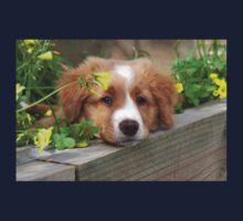 Cute puppy lying in the garden Kids Tee