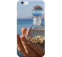 Hands hold a bottle with seashells on the beach iPhone Case/Skin