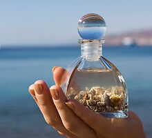 Hands hold a bottle with seashells on the beach by PhotoStock-Isra