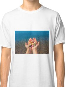 Hands present seashells on the beach first person view  Classic T-Shirt