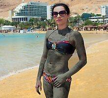 Young Caucasian tourist covered in therapeutical mud at a Dead Sea  by PhotoStock-Isra