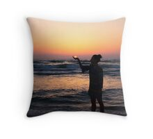woman holds the sun as it sets in the palm of her hand  Throw Pillow