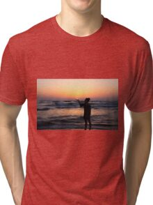 woman holds the sun as it sets in the palm of her hand  Tri-blend T-Shirt
