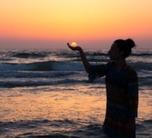 woman holds the sun as it sets in the palm of her hand  Sticker