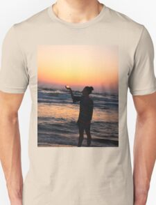 woman holds the sun as it sets in the palm of her hand  T-Shirt