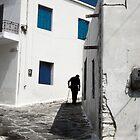 Old man turning the corner in Mykonos Greece by milton ginos