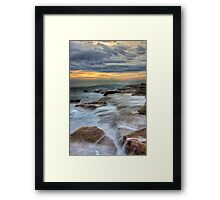 The eternal play between land and sea Framed Print