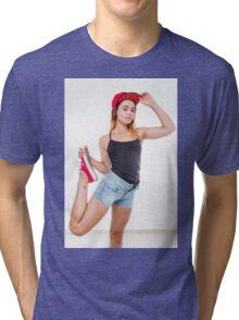 Flexible female teen with red baseball cap wearing black top  Tri-blend T-Shirt
