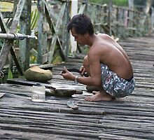 Manuel sharpens his tools - Iban Longhouse by Trishy