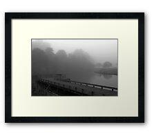 Lonely bench on misty pier Framed Print