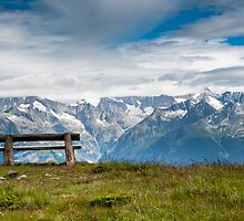 empty park bench in high alps by peterwey