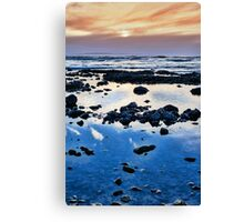 calm yellow sunset over rocky beach Canvas Print