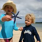 Josie and Kye discover starfish on a fijian beach by Ian Robinson