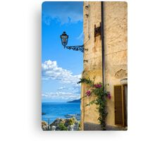 House with bougainvillea, street lamp and distant sea Canvas Print