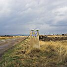 old pilgrim's trail marker beneath stormy clouds by Christopher Barton
