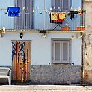 Italian windows with hanging washing and bench by Silvia Ganora