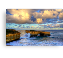 A wave crashes the London Arch at sunrise Canvas Print