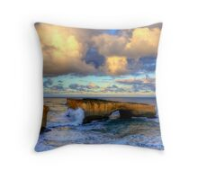 A wave crashes the London Arch at sunrise Throw Pillow