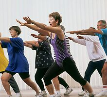 mature aged people exercising with personal trainer by Brian McInerney