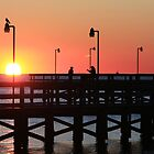 Two fishermen sillouhetted on the pier at sunrise by Timothy Gass