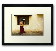 Exiled monk on his mobile phone Framed Print