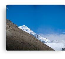 Trekkers walking up hill side with snow capped mountain in the background  Canvas Print