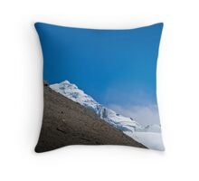 Trekkers walking up hill side with snow capped mountain in the background  Throw Pillow