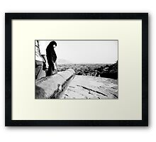 Girl  curiously looking at a canon  Framed Print
