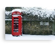 red phone box on a snowy London Canvas Print