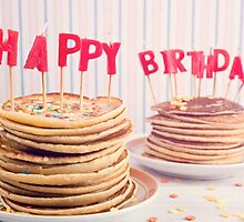 Pancakes piled up decorated with birthday candles by Elisabeth Coelfen