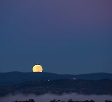Full moon sets behind mountains by glennsphotos