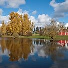 Red Barn, Fall Colors and Puffy Clouds Reflected in a Pond by Jeff Goulden