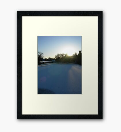 As the sun sets on the snowy village pond ...  Framed Print