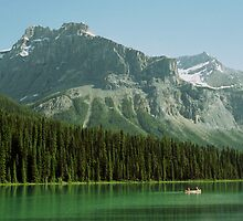 A Canoe Glides on Emerald Lake by DMHImages