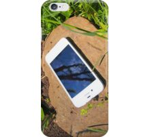 White smartphone on a rock in a meadow iPhone Case/Skin