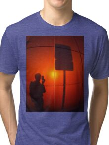 The silhouette of a man on a red-orange wall Tri-blend T-Shirt