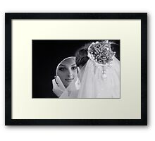 Beautiful young bride looking in the mirror Framed Print