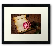 Pink rose and a parchment Framed Print