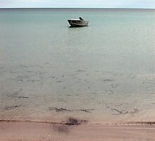 lone dingy at island beach by aurelie k