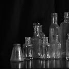 nine glass bottles on black by Clare Colins
