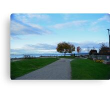 Beautiful crescent beach in late summer in White Rock, BC. Landscape picture of green grasses, blue sky, early fall yellow leaves tree and sea.  Canvas Print