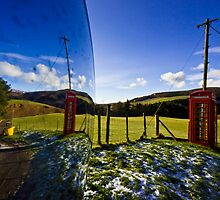 Red phonebooth and Scottish landsape reflecting in a convex mirror by Gabor Pozsgai