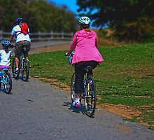 Family riding bikes in Shoreline park by happyphotos