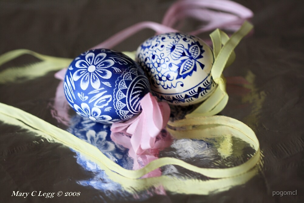 two traditional hand-painted Czech blue and white Easter eggs reflect on silver foil by pogomcl