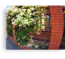 Facade of the building with a brick wall with flowers Canvas Print