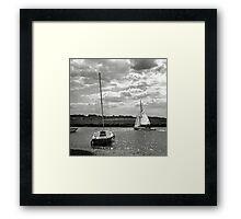 A yacht returns to harbour at Blakeney, Norfolk, UK Framed Print