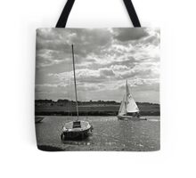 A yacht returns to harbour at Blakeney, Norfolk, UK Tote Bag